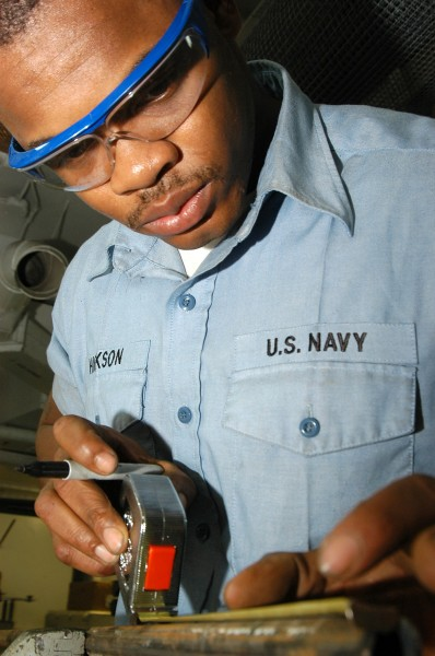 US Navy 031208-N-6278K-001 Hull Technician 3rd Class Thomas Hickson from Marion, S.C., measures a piece of metal in the machine shop aboard USS George Washington (CVN 73)