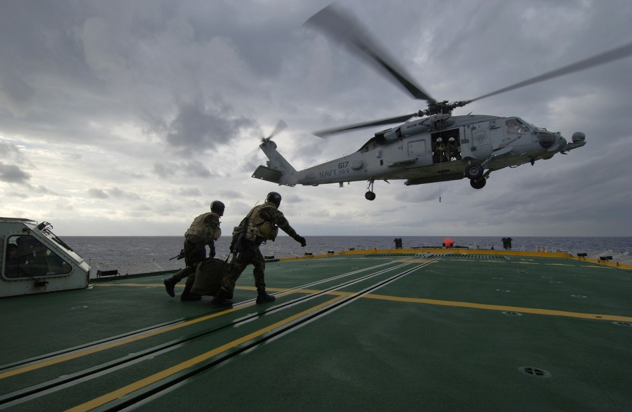 US Navy 040212-N-5319A-007 Members assigned to Explosive Ordnance Disposal Mobile Unit Six (EODMU 6) carry their fast rope back to an HH-60H Seahawk helicopter