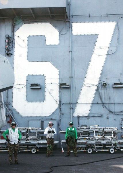US Navy 040306-N-4374S-010 Sailors observe flight operations while standing in front of the island superstructure aboard the aircraft carrier John F. Kennedy
