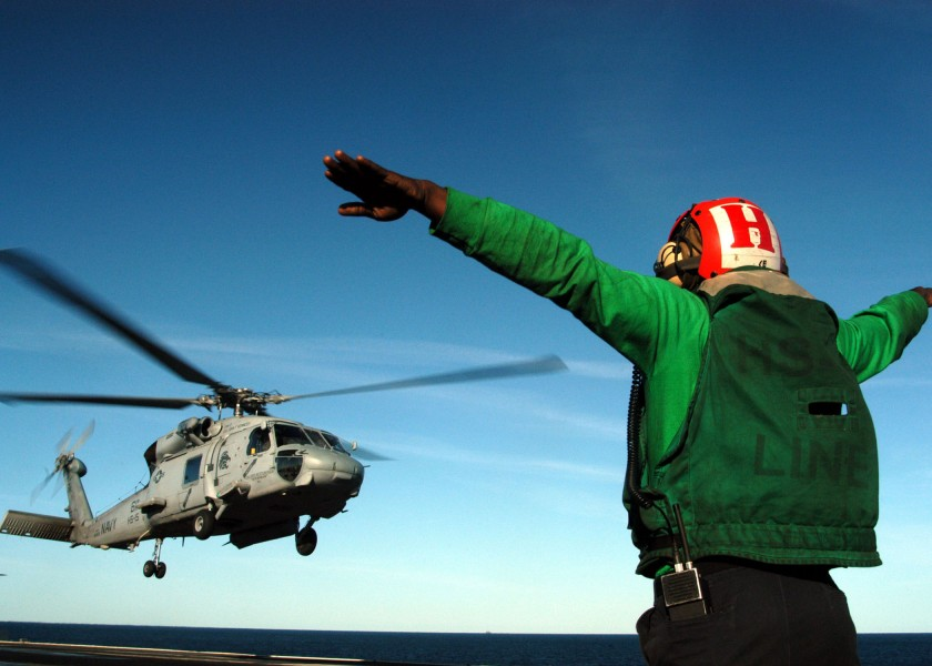 US Navy 040308-N-8704K-002 A Landing Signal Enlisted (LSE) signals an SH-60F Seahawk assigned to the