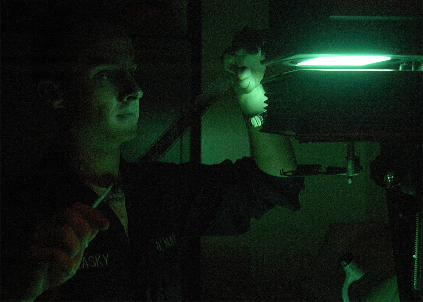 US Navy 040413-N-1522S-008 Photographer's Mate Airman Jason R. Zalasky, of Lake Hopatcong, N.J., views film negatives in a photographic darkroom aboard USS George Washington (CVN 73)