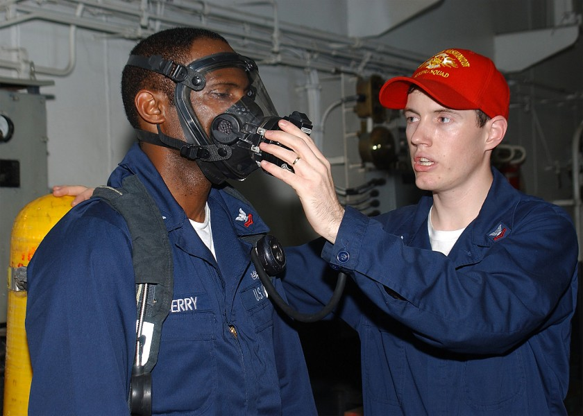 US Navy 040518-N-3992H-007 Damage Controlman 2nd Class Dustin Woolever of Lancaster, Ohio, demonstrates the proper wear and use of the Self Contained Breathing Apparatus (SCBA)