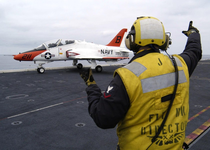 US Navy 040623-N-6817C-040 An Aviation Boatswain's Mate directs a T-45A Goshawk assigned to Training Air Wing Two (TW-2) on the flight deck of USS Abraham Lincoln (CVN 72)