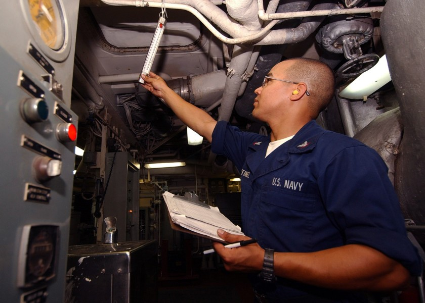 US Navy 040701-N-4374S-003 Engineman 3rd Class Carlos Martinez checks the temperature in main engine room two