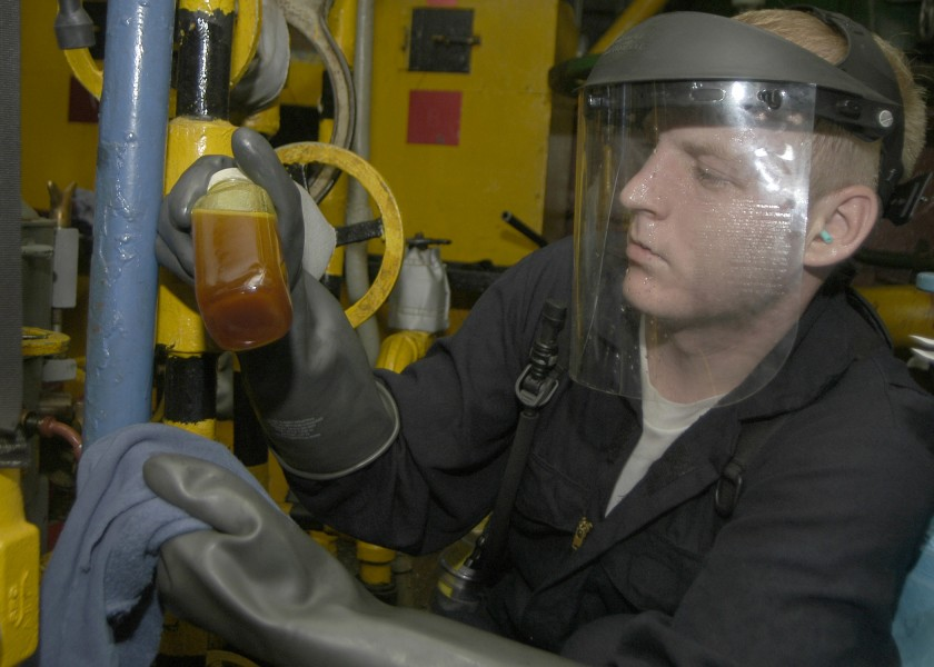 US Navy 040731-N-4549D-003 Machinist 3rd Class James Mercer of Jacksonville Fla., extracts a lube oil sample from the main engine in the number Three Main Machinery Room
