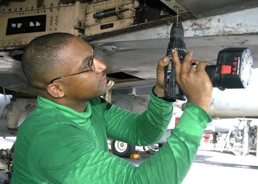 US Navy 040731-N-4565G-002 Aviation Structural Mechanic 2nd Class Kelvin Santos of Bronx, New York replaces rivets on the tail hook hydraulic system of an F-A-18B Hornet