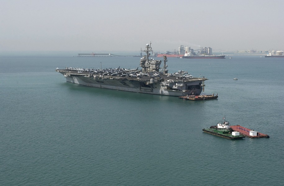 US Navy 040810-N-1348L-002 Tug boats and barges stand by as the aircraft carrier USS John F. Kennedy (CV 67) prepares to get underway after a five-day port visit to Bahrain