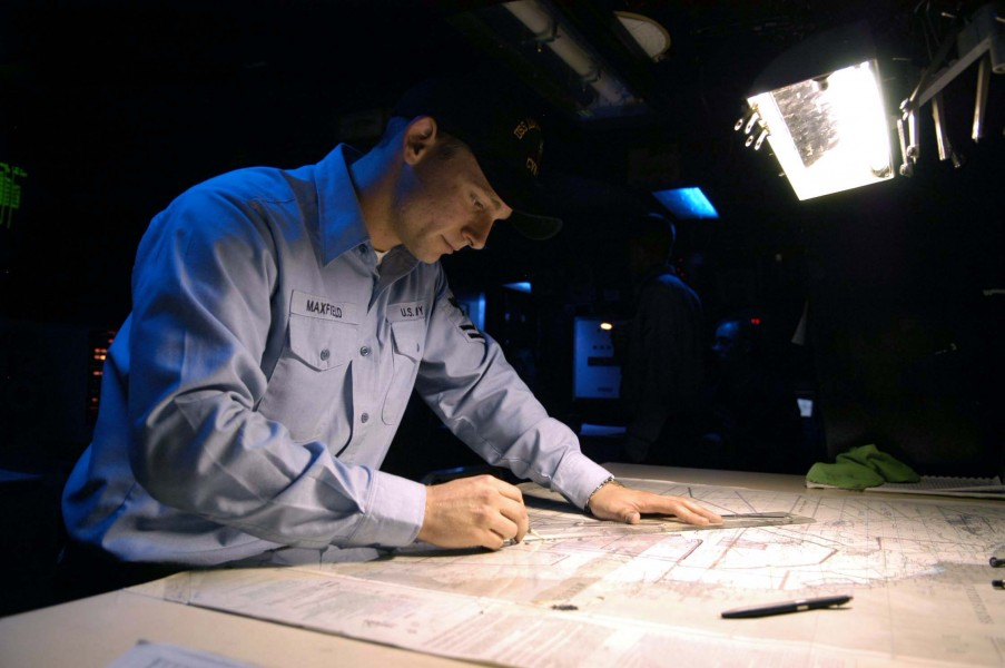US Navy 040818-N-0499M-001 Operation Specialist 2nd Class Ryan E. Maxfield plots the ship^rsquo,s position on a navigational chart