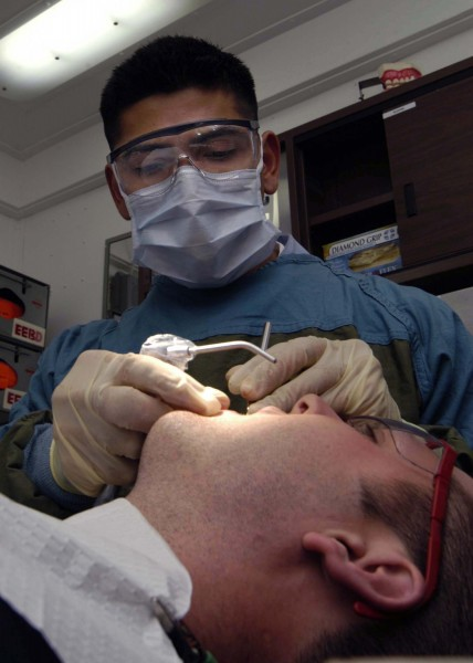 US Navy 040824-N-5384B-056 Dental Technician 3rd Class Carlos M. Valverde, of Nicaragua, performs a routine semi-annual checkup and cleaning on the teeth of a Sailor