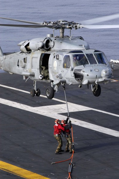 US Navy 040825-N-9228K-015 Two Aviation Ordnancemen assigned to G-1 Weapons division aboard the aircraft carrier USS Abraham Lincoln (CVN 72) attach sling load assemblies to an HH-60H Seahawk