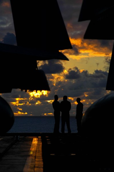 US Navy 041023-N-4166B-041 Pilots aboard the aircraft carrier USS Abraham Lincoln (CVN 72), assemble on the bow of the ship as the sunsets on the western Pacific Ocean