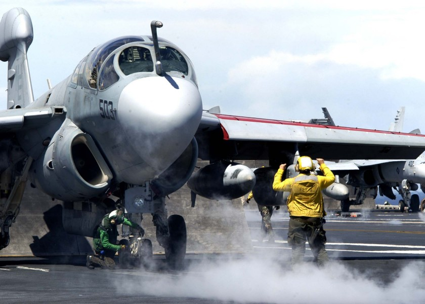 US Navy 041026-N-0499M-096 An Aviation Boatswain's Mate directs an EA-6B Prowler assigned to the Lancers of Electronic Attack Squadron One Three One (VAQ-131) onto a catapult