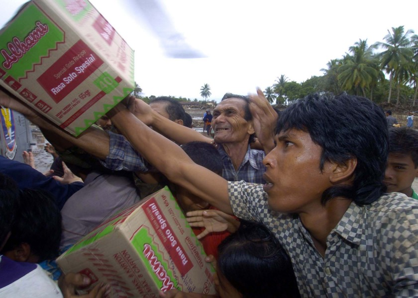 US Navy 050108-N-9593M-145 Indonesian citizens reach for the food that is being unloaded from an SH-60F Seahawk helicopter