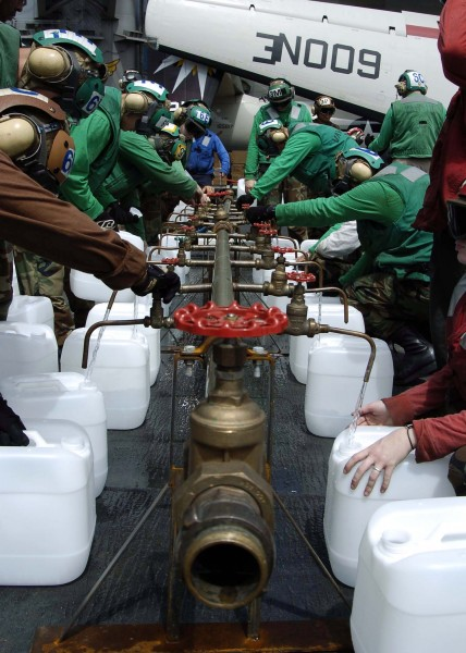 US Navy 050109-N-0057P-109 Crew members aboard USS Abraham Lincoln (CVN 72) fill jugs with purified water from a Potable Water Manifold
