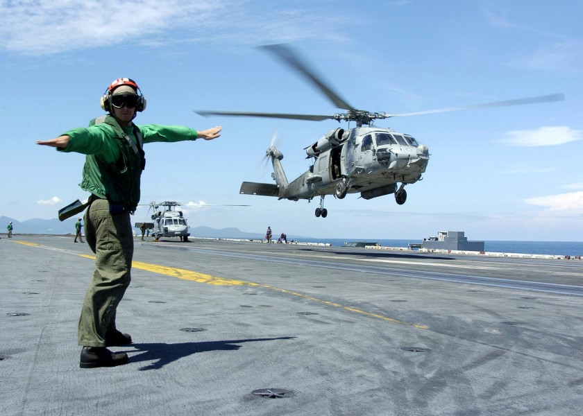 US Navy 050111-N-6817C-190 A Landing Signals Enlisted man directs an HH-60H Seahawk to a safe landing on the flight deck aboard USS Abraham Lincoln (CVN 72)