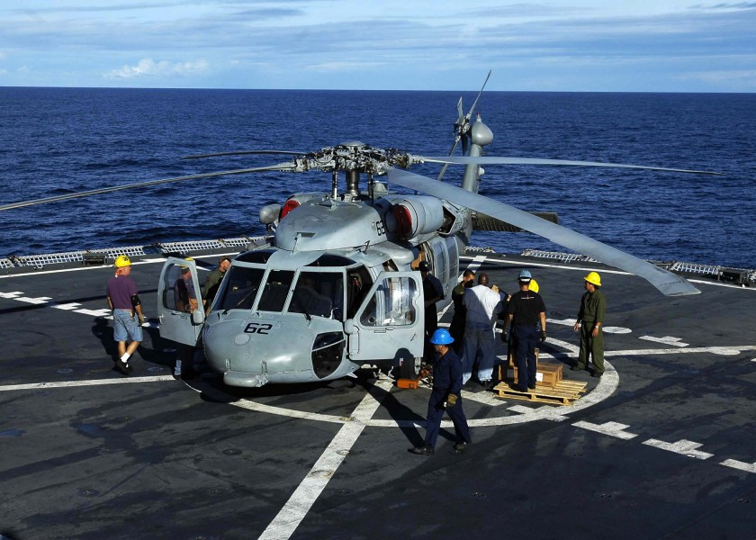US Navy 050112-N-6074Y-015 Merchant Marine Sailors load a MH-60S Knighthawk helicopter with relief supplies prior to being flown to villages on the island of Sumatra, Indonesia