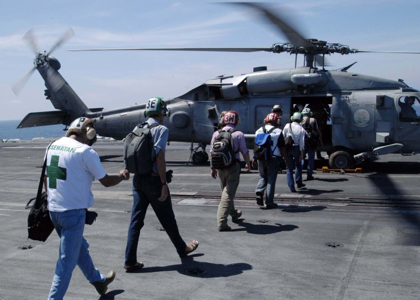 US Navy 050114-N-1229B-064 Military and United Nations personnel board an HH-60H Seahawk aboard USS Abraham Lincoln (CVN 72)