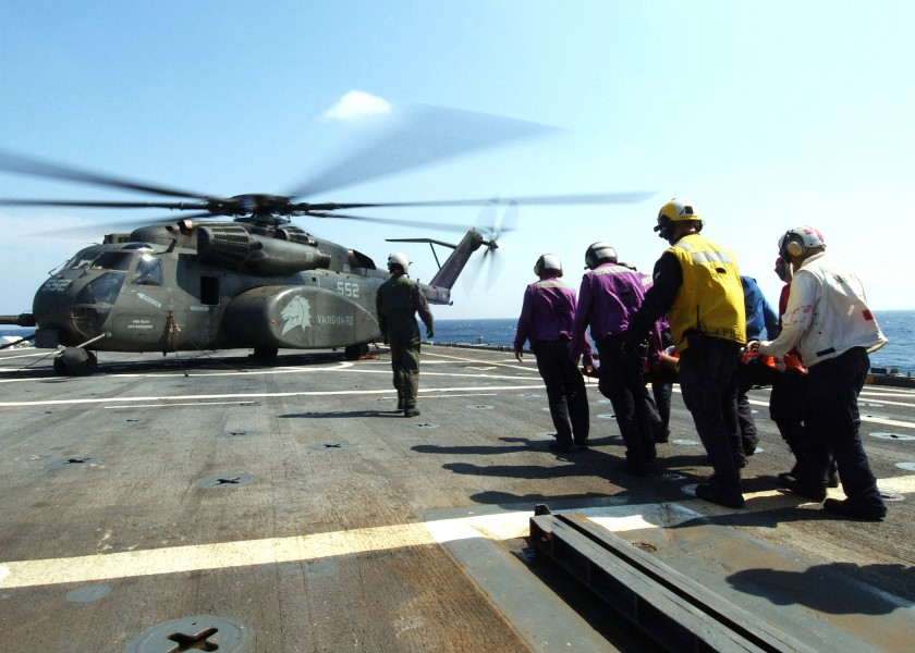 US Navy 050508-N-4374S-003 Stretcher bearers assigned to the amphibious transport dock ship USS Trenton (LPD 14), carry an 83-year old civilian, to an MH-53E Sea Dragon helicopter
