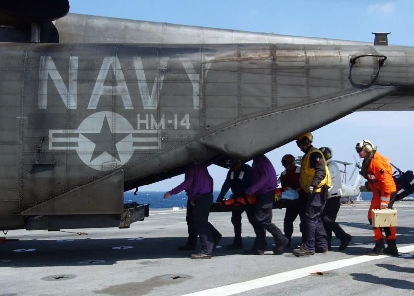 US Navy 050508-N-4374S-004 Stretcher bearers assigned to the amphibious transport dock ship USS Trenton (LPD 14), carry an 83-year old civilian, to an MH-53E Sea Dragon helicopter