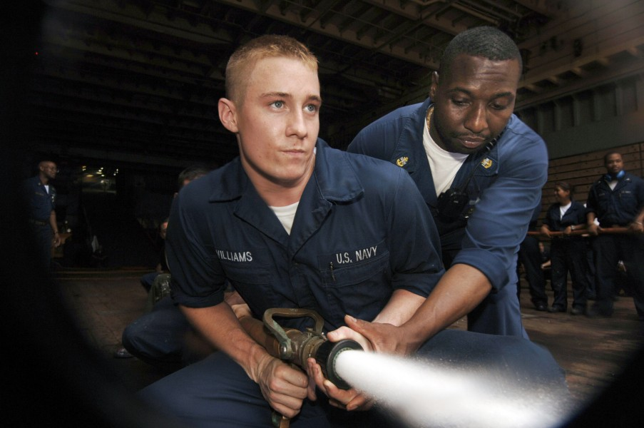 US Navy 050531-N-4309A-142 Chief Damage Controlman Horace Smith provides proper hose handling techniques to Interior Communications Technician Fireman Jarad Williams during a fire drill