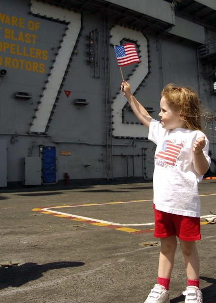 US Navy 050704-N-0057P-039 A young child holds up an American Flag in a show of patriotism on the flight deck aboard the Nimitz-class aircraft carrier USS Abraham Lincoln (CVN 72)