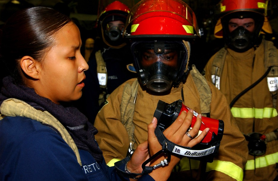 US Navy 050713-N-6125G-004 Damage Controlman 3rd Class Louchelle Loretto, left, trains a fire party on how to use the new Naval Firefighting Thermal Imager (NFTI) during a general quarters drill