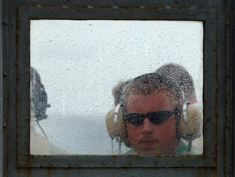 US Navy 050718-N-5345W-055 A Sailor assigned to the Air Department looks through the rain-spattered windshield glass on the Landing Signal Officer (LSO) platform during flight operations