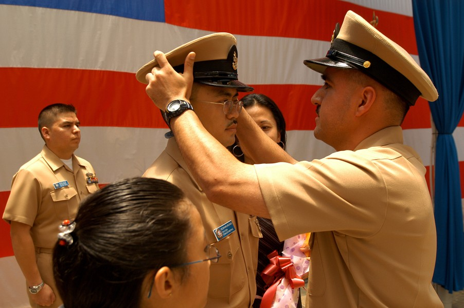 US Navy 050916-N-4205W-003 Chief Information Systems Technician Luis King places a new chief petty officer (CPO) cover on the head of Frank Agcaoili during a CPO pinning ceremony