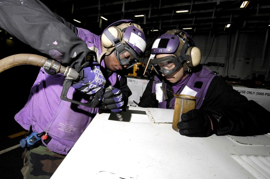 US Navy 060107-N-7981E-039 Airman Recruit Gabriel Salidomendoza and Airman Recruit Gerald Brown fuel support equipment in the hangar bay