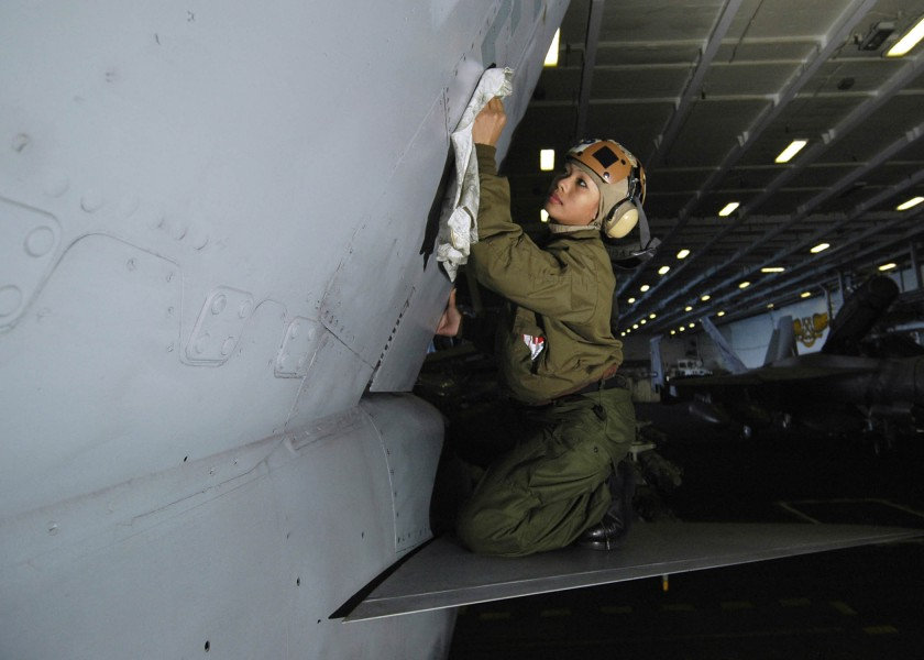 US Navy 060119-N-7981E-034 Airman Jinxqueenifer Garcia, cleans the vertical stabilizer of an F-A-18C Hornet in the hangar bay of the Nimitz-class aircraft carrier USS Abraham Lincoln (CVN-72)