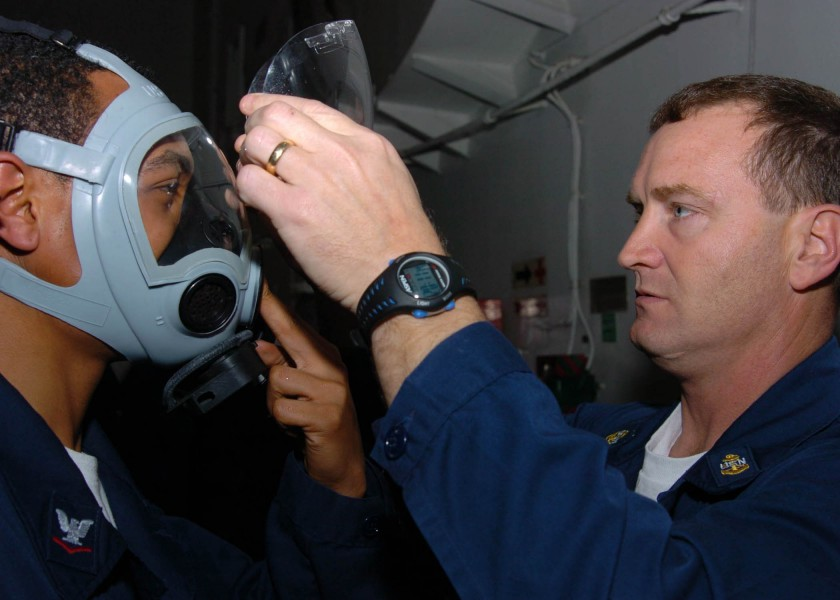 US Navy 060127-N-9641C-002 Chief Damage Controlman, John Brooks, removes the face shield from a Sailor^rsquo,s MCU-2-P gas mask