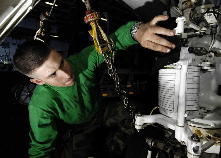 US Navy 060306-N-7981E-002 Aviation Structural Mechanic Airman Allen Strohm wipes excess grease from the landing gear of an E-2C Hawkeye