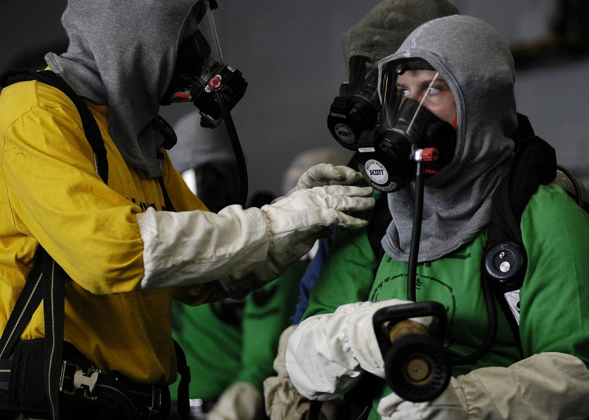 US Navy 060315-N-5837R-055 A nozzle man listens to the scene leader for instructions on battling a simulated fire in the hangar bay