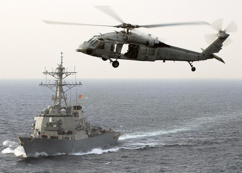 US Navy 060325-N-5837R-169 A MH-60S Seahawk helicopter assigned to the Golden Falcons of Helicopter Anti-Submarine Squadron Two (HS-2), flies by the guided-missile destroyer USS Russell (DDG 63)