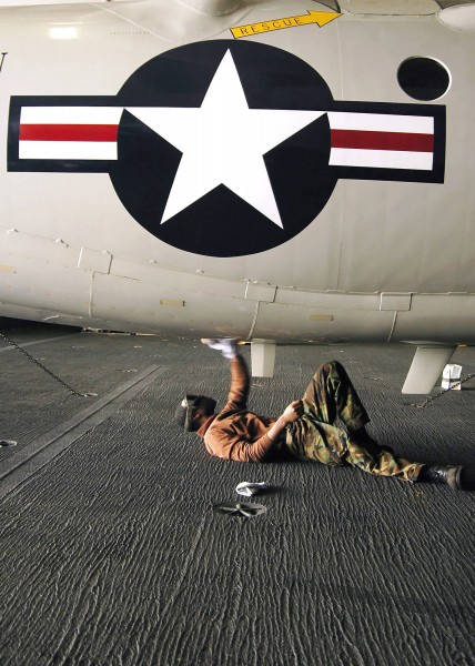 US Navy 060331-N-7981E-044 Airman Elliot Littles cleans the underside of an E-2C Hawkeye assigned to Carrier Airborne Early Warning Squadron One One Six (VAW-116)