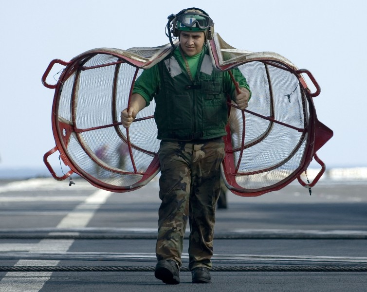 US Navy 060416-N-4166B-045 A Sailor assigned to Air Department carries intake duct screens on the flight deck aboard the Nimitz-class aircraft carrier USS Abraham Lincoln (CVN 72)