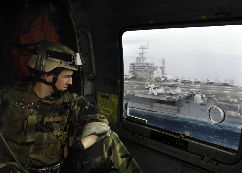 US Navy 060502-N-0499M-022 Lt. John C. Laney assigned to Explosive Ordnance Disposal Detachment 9, looks out the window of an SH-60F Seahawk helicopter