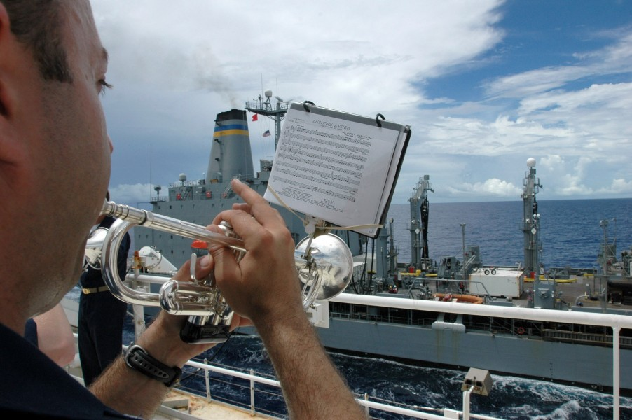 US Navy 060516-N-9076B-024 Musician 1st Class Brian Grondell plays Anchors Away during an underway replenishment between the USNS Pecos and USNS Mercy