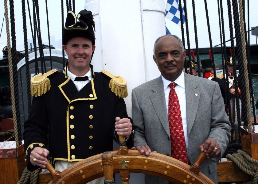 US Navy 060623-N-5367L-002 Commanding Officer, Cmdr. Thomas C. Graves, and Assistant Secretary of the Navy for Installations and Environment, the Honorable B.J. Penn, man the helm aboard USS Constitution