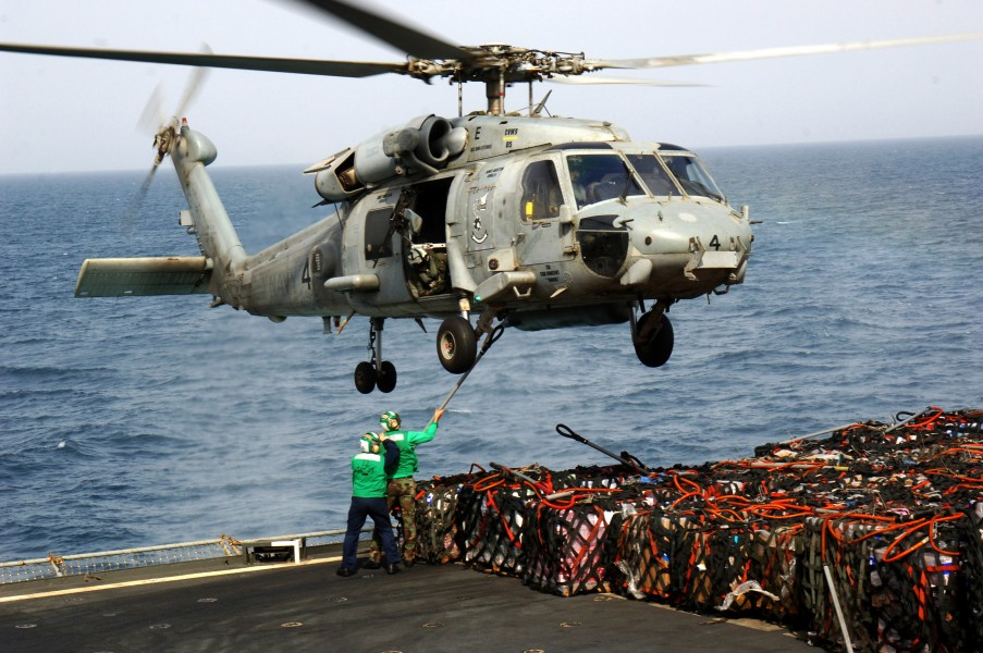 US Navy 070603-N-3262C-006 Sailors from Helicopter Squadron Combatant (HSC) 23 attach a hook to the bottom of an SH-60 Seahawk