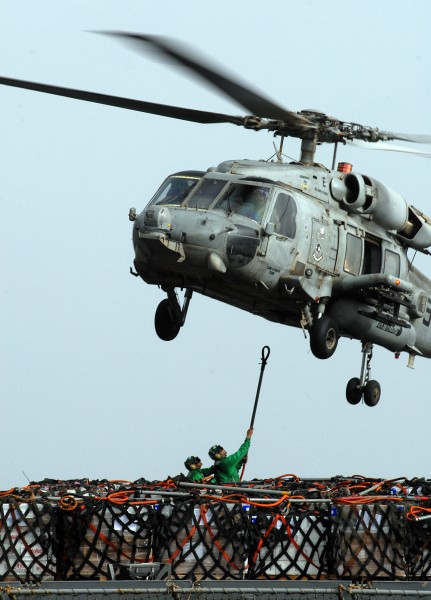 US Navy 070616-N-3038W-183 Sailors from Military Sealift Command fast combat support ship USNS Bridge (T-AOE 10) attach cargo nets holding pallets of supplies to an HH-60H Seahawk during a vertical replenishment