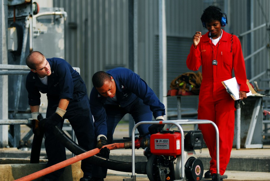 US Navy 070626-N-1688B-403 Damage Controlman 2nd Class Breanna Witherspoon watches for mistakes while timing Sailors on an event using the P-100 fire pump