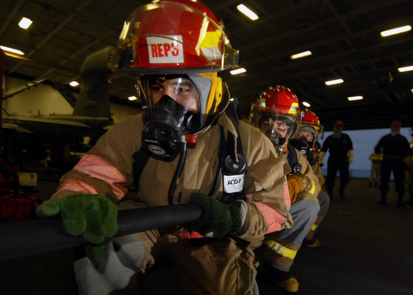 US Navy 070804-N-7981E-190 Members of a repair locker hose team advance on a simulated fire in the hangar bay of Nimitz-class aircraft carrier USS Abraham Lincoln (CVN 72), during a General Quarters (GQ) drill