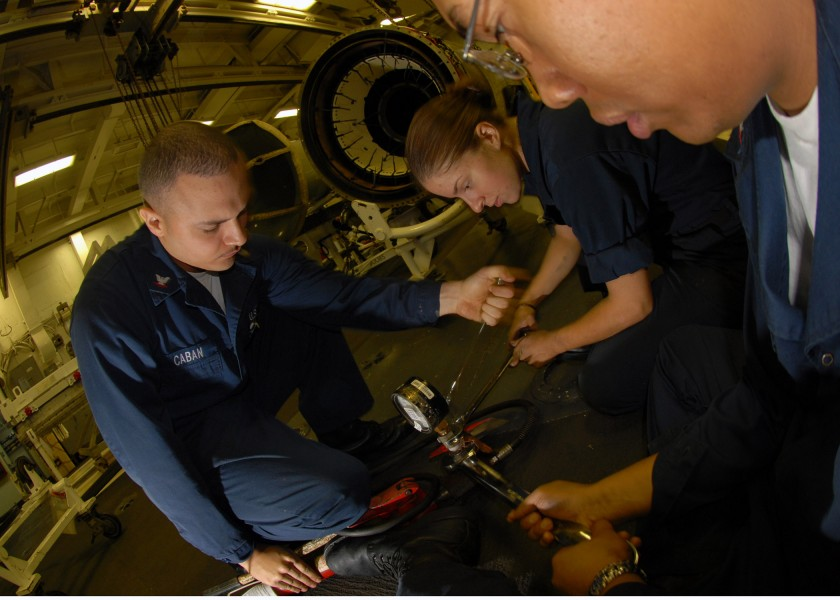 US Navy 070808-N-2910W-001 Sailors use wrenches to calibrate pressure valve to the turbine from a hydraulic pump in the Jet Shop aboard Nimitz-class aircraft carrier USS Abraham Lincoln (CVN 72)