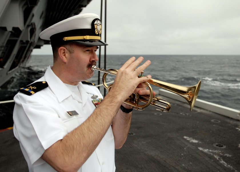 US Navy 070819-N-7981E-122 Chief Warrant Officer 3 Rob Holland plays taps at the completion of a burial at sea ceremony aboard Nimitz-class aircraft carrier USS Abraham Lincoln (CVN 72)