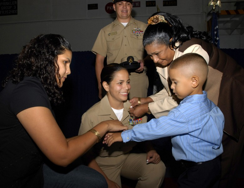 US Navy 070921-N-4133B-051 Family members of Chief Machinist's Mate Orlyn Fernandez pin anchors on her collar during a pinning ceremony held in the hangar bay aboard USS Ronald Reagan (CVN 76)