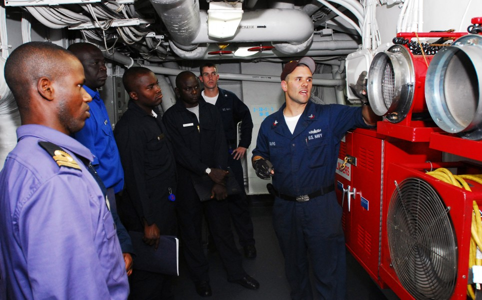 US Navy 071101-N-8933S-015 Damage Controlman 2nd Class Adam Burg talks about the Ram Fans used to remove smoke from an area after a fire is extinguished to Nigerian Sailors
