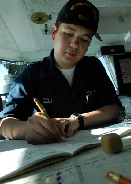 US Navy 080124-N-7981E-085 Quartermaster Seaman Jonathan Izzett makes entries to the ship's position log while assisting the Quartermaster of the Watch on the bridge of the USS Abraham Lincoln