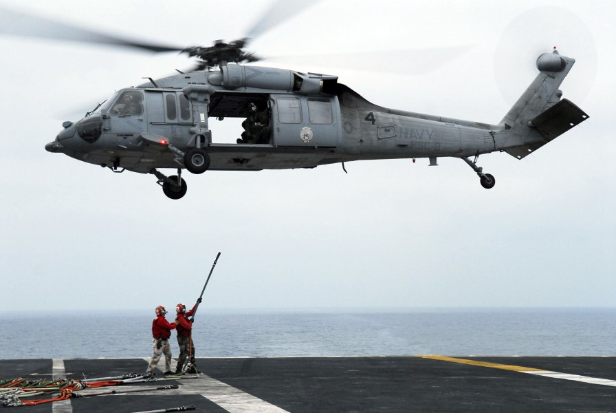 US Navy 080625-N-2610F-084 Flight Deck Gunner Chief Warrant Officer Eric Richmond, left, and Aviation Ordanceman 3rd Christopher Wozniak connect hoisting slings to an MH-60S Seahawk