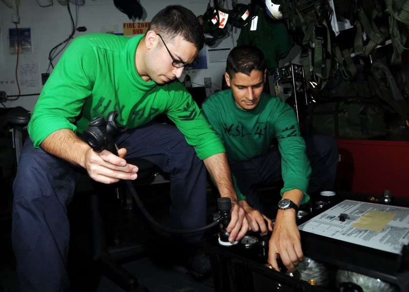 US Navy 080627-N-9898L-020 Aircrew Survival Equipmentman 2nd Class Joe Quintero, left, and Aircrew Survival Equipmentman 1st Class Brian Hawks fill emergency breathing bottles for survival vests